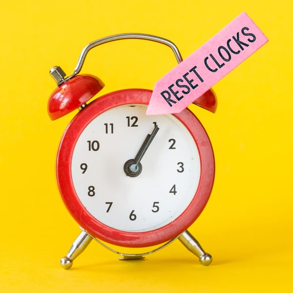 Red alarm clock against a yellow background with a pink arrow pointing at it with the words 'reset clocks' on it.