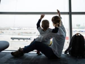 Mom son waving airport window