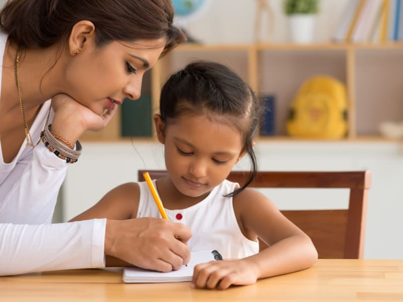 Mom teaching daughter using book and pencil