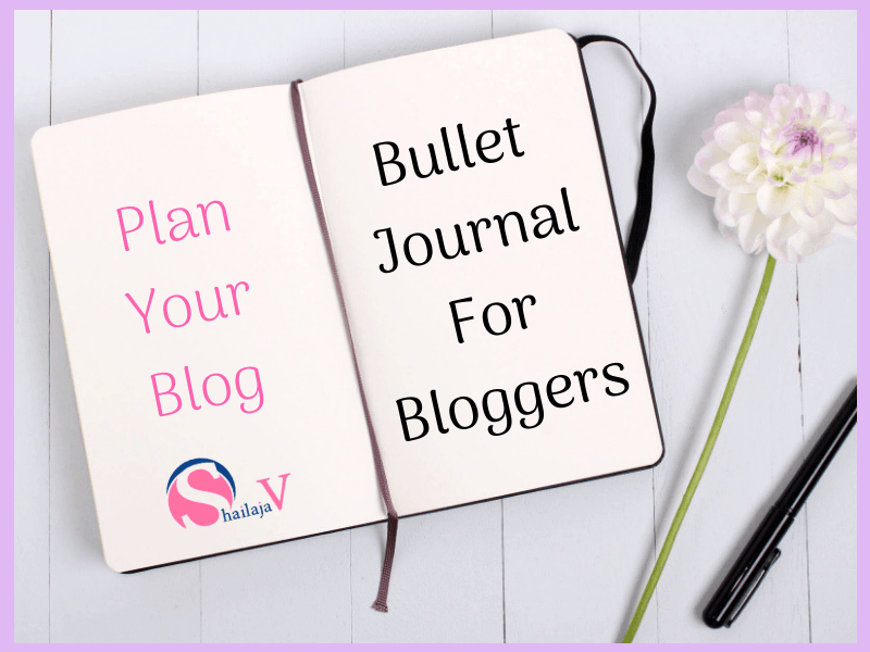 Plan your Blog- Bullet Journal for Bloggers- White open notebook placed on table next to a flower and a pen