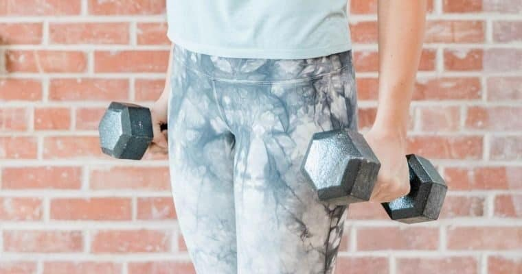 woman wearing fitness gear and holding dumbbells