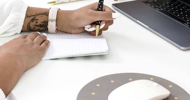 A person writing in a notebook next to a laptop and a mouse pad on a desk. The post is talking about how to write the best headlines for your blog.