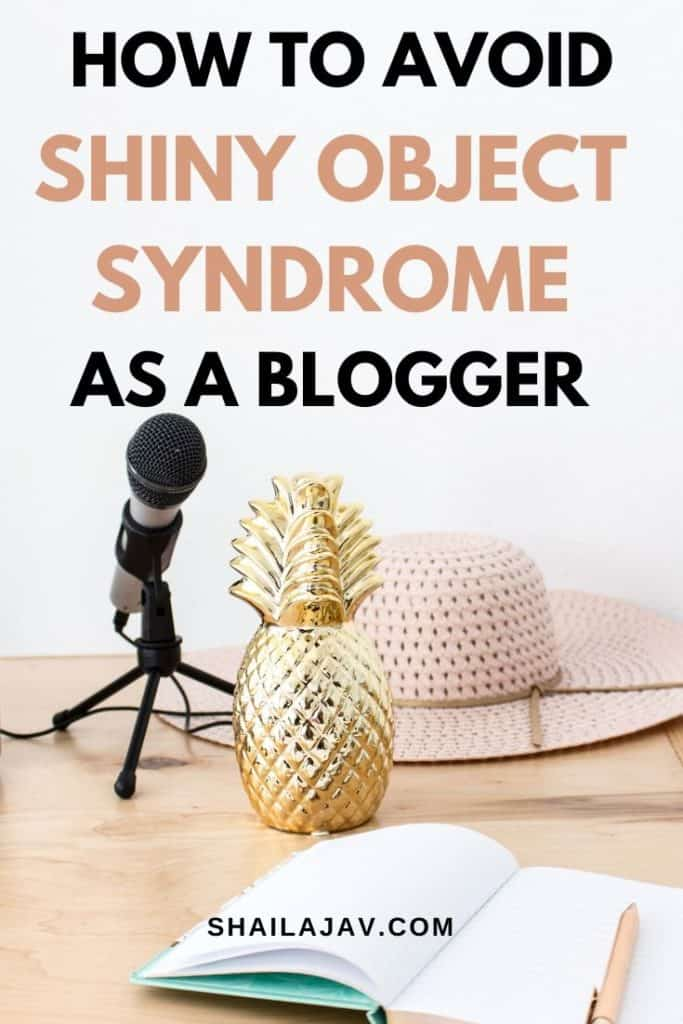 A desk which shows a microphone, a hat and a shiny pineapple centre piece next to an open notebook. The content talks about how to avoid shiny object syndrome.