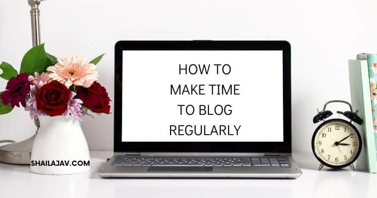 Open laptop next to a clock and a vase of flowers