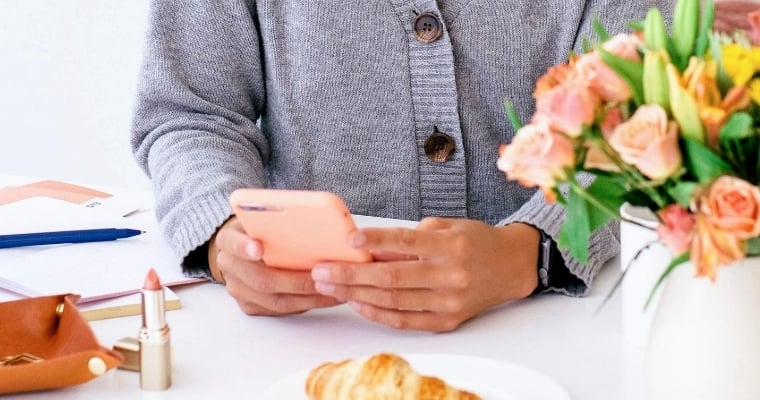 Woman looking at phone and tips on how to reduce your screen time