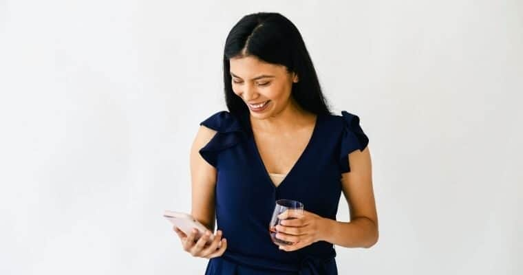 Woman smiling and looking down at her phone