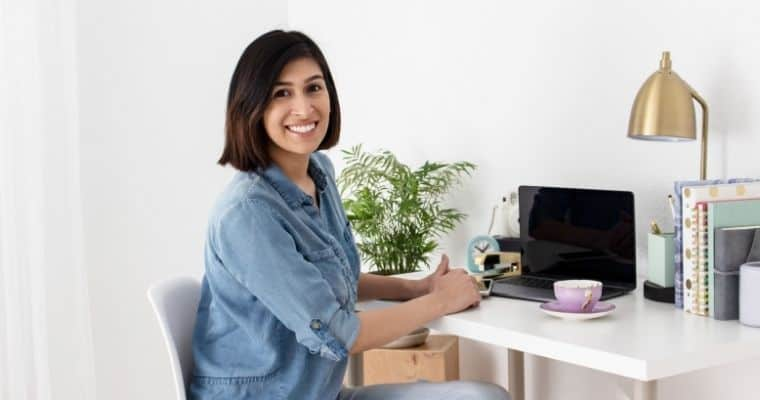 Successful Blogging secret featuring a smiling woman blogger seated at her desk with a laptop