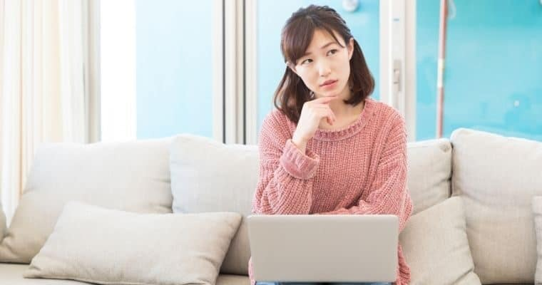 Woman seated on couch with laptop on knee and thinking