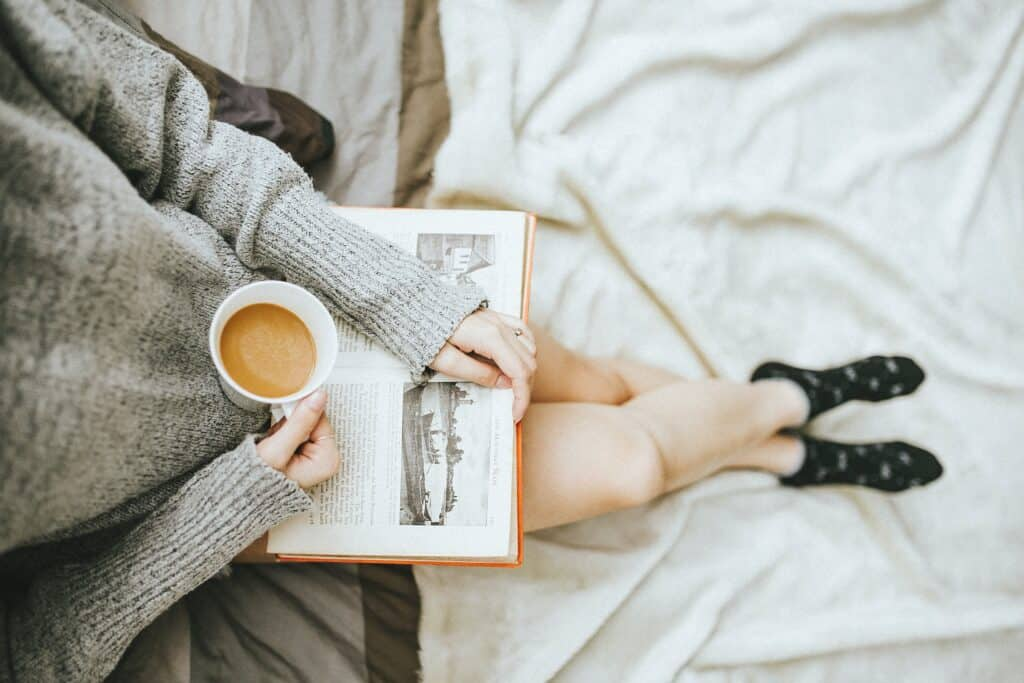 woman holding cup of coffee in right hand and reading book open on her lap
