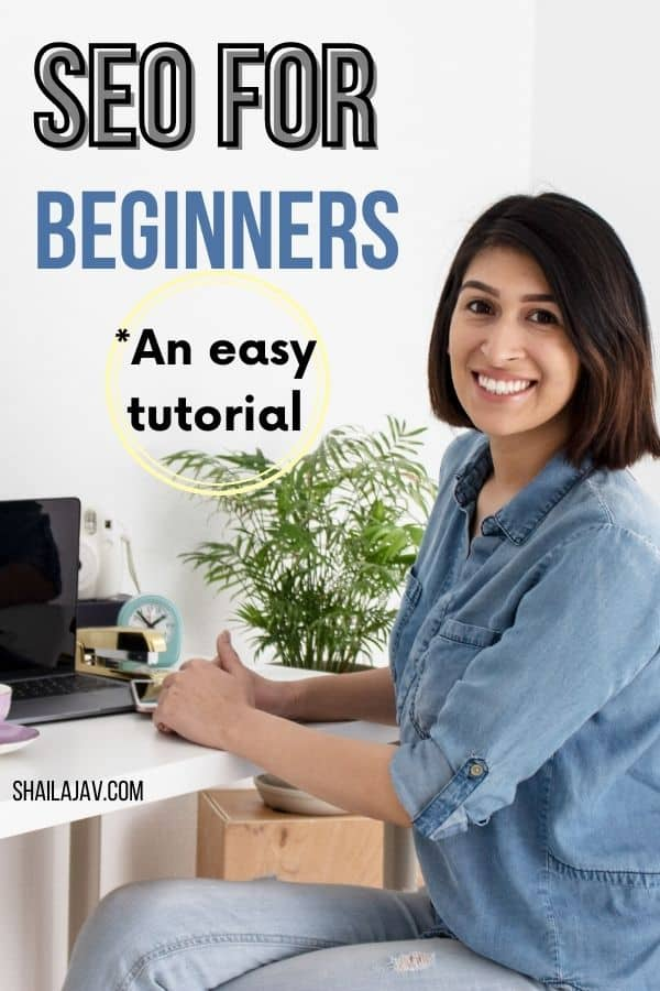 Woman smiling into the camera while seated at a work desk which has a laptop, a camera, a clock and a plant on it. SEO for Beginners