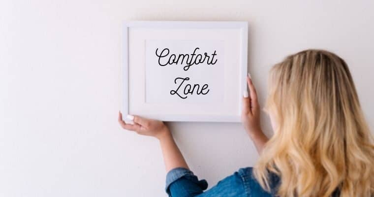 Woman hanging up a framed picture with the words comfort zone inside it